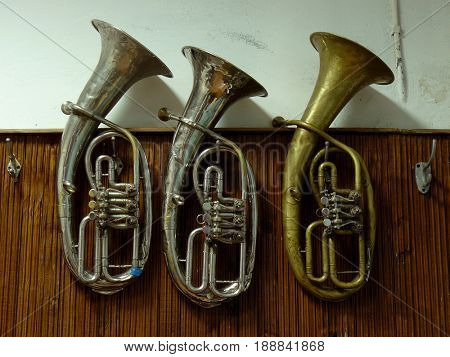 three old baritone horns hanging on the wall