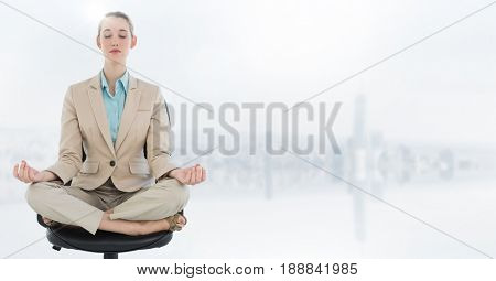 Digital composite of Business woman meditating on chair with flare against blurry white skyline