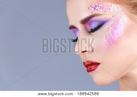Beautiful young woman with creative makeup on color background, closeup