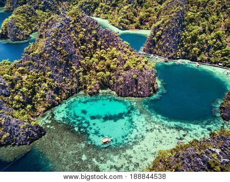 Aerial top view of lagoon with boat surrounded by rocks and turquoise sea. Palawan