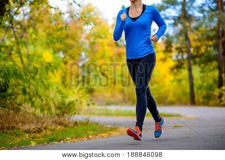 Young Woman Running in the Beautiful Autumn Park at Warm Sunny Day. Active Lifestyle Concept.
