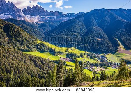 Val de Funes valley. Lovely sunny warm autumn day. Odle mountain peaks and forested mountains surrounded by green Alpine meadows