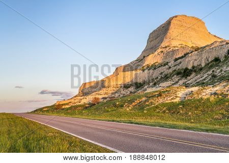highway through Scotts Bluff National  Monument in Nebraska, spring scenery with sunset light