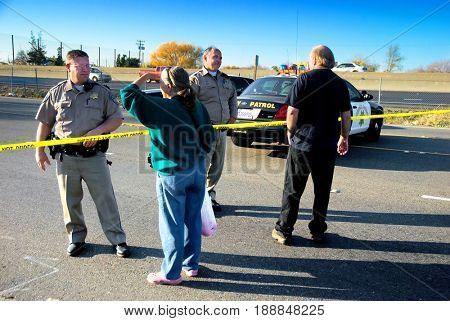 SACRAMENTO, CALIFORNIA, USA - December 2, 2009: Curious onlookers ask California Highway Patrol deputies questions at a crime scene