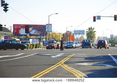 SACRAMENTO, CALIFORNIA, USA - December 2, 2009: Sacramento police officer directing traffic away from a cordoned off section of the street during a crime investigation
