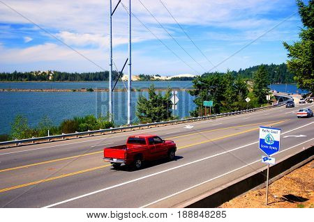 HIGHWAY 101, COOS BAY, OREGON, USA - September 3, 2009: Car drives on Highway 101 with a Pacific Coast Scenic Byway sign in the foreground