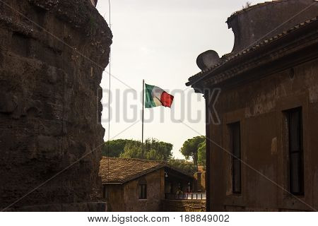 Italian flag waving in the air behind buildings