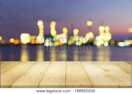 Oil refinery factory montage with wood table top at twilight with sky background.