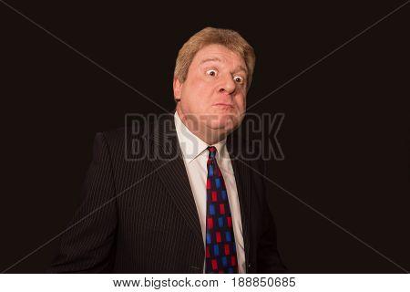 Studio shot of angry senior businessman against black background