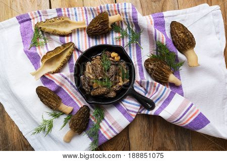 Delicious black morel mushrooms in skillet on rustic wooden table top view. Diet vegetarian food.