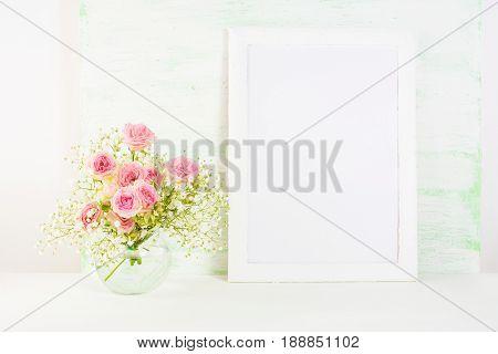 White frame mockup with blooming Rue Anemone. Empty frame mock up for presentation artwork. Template framing for modern art.