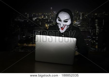 Computer hacker stealing data from laptop (Concept for network security)