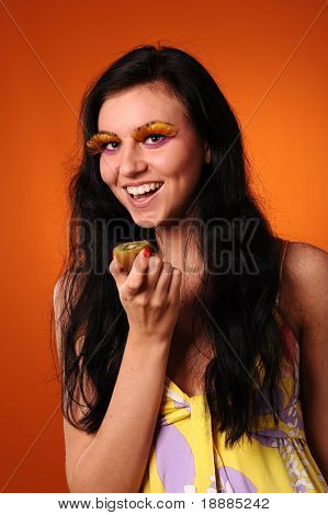young beautiful woman want to eat fresh green kiwi, isolated on orange background