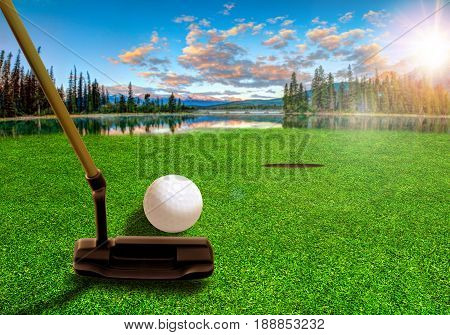 Golfer using a putter club to hit a golf ball on a beautiful golf course with lakes and mountain scenery in the early morning.  3D rendering of fictitious golf course.