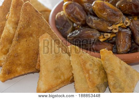 a plate of dates surrounding with samosa