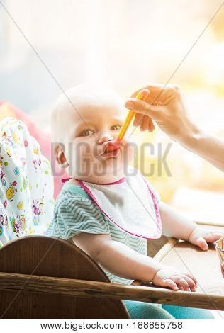 mother feeds funny baby from a spoon sitting in the wood chair