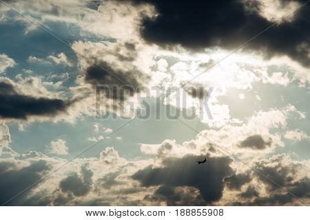 The plane flies under the rays of the sun which can be seen through the cumulus clouds.
