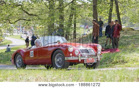 STOCKHOLM SWEDEN - MAY 22 2017: Red MG MGA 1500 Roadster classic car from 1958 driving on a country road in the public race Gardesloppet in the forests at Djurgarden Stockholm Sweden. May 22 2017