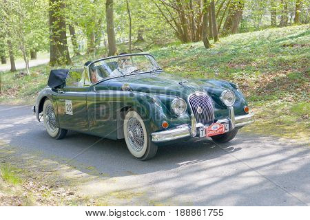 STOCKHOLM SWEDEN - MAY 22 2017: Dark green Jaguar XK 150 classic car from 1960 driving on a country road in the public race Gardesloppet in the forests at Djurgarden Stockholm Sweden. May 22 2017