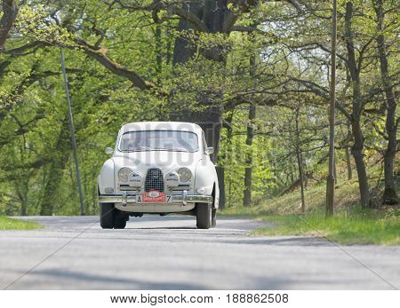 STOCKHOLM SWEDEN - MAY 22 2017: White Saab Sport classic car from 1962 driving on a country road in the public race Gardesloppet in the forests at Djurgarden Stockholm Sweden. May 22 2017