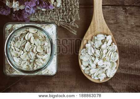Oat flakes or oatmeal in glass bottle on rustic wood table. Rolled oat is clean food for health lover people. Prepare oat flakes for bakery or cooking.Natural organic food in vintage style concept.Oat flake, oatmeal background and texture.
