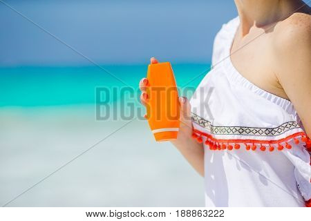 Closeup suncream bottle in female hands background turquoise water
