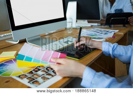 Close-up of female graphic designer using graphics tablet at desk in office