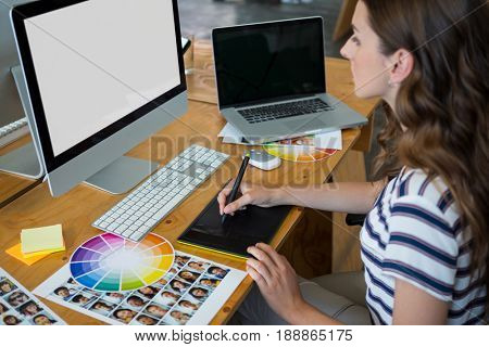 Female graphic designer using graphics tablet at desk in office