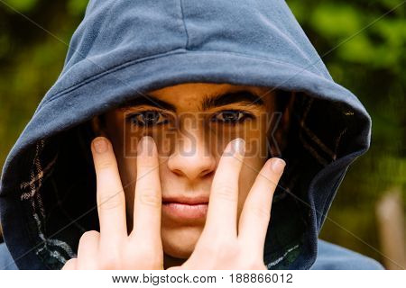 Attractive confident teenage boy with hoodie over head doing victory gesture with his hands