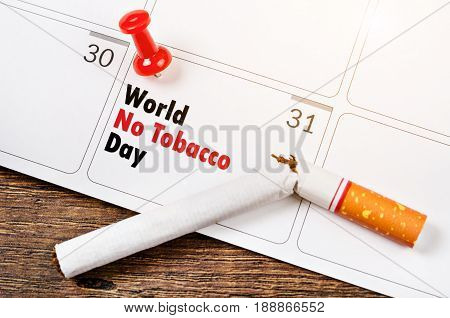 Push pins marked date Quit Smoking on calendar 31th May with tobacco. World No Tobacco Day.