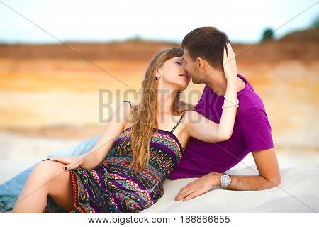 Lovers lying and kissing on the beach. romantic travel honeymoon vacation summer holidays. young girl dressed in a colorful dress and man in a violet t-shirt. they embracing outdoors