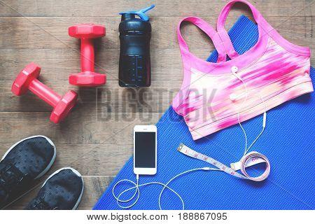 Sport equipments. Sport bra. Smartphone and sport shoes on wood floor