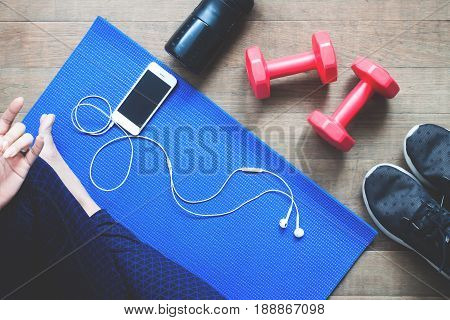 Fitness woman using mobile device Sport equipment Bottle water on wood floor
