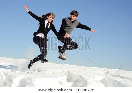 Two teenagers jumping on the snow field