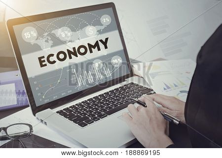 business hand typing on computer keyboard with Economy homepage on the screen finance and banking website web page concept.