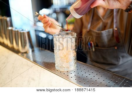 alcohol drinks, people and luxury concept - bartender with glass pouring syrup to stirrer and preparing cocktail at bar counter