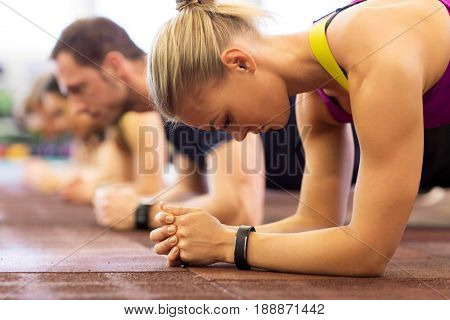 fitness, sport, exercising, people and healthy lifestyle concept - close up of woman with heart-rate tracker at group training doing plank exercise in gym