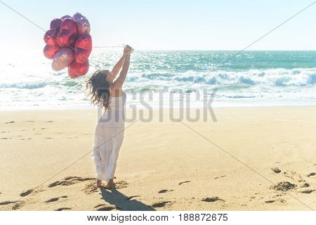 Young woman in white dress holding red balloons on the beach, enjoying sunny windy day.
