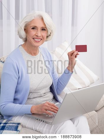 Beautiful woman using laptop computer, showing credit card and smiling to camera. Elderly woman using credit card number for buying goods in online market.