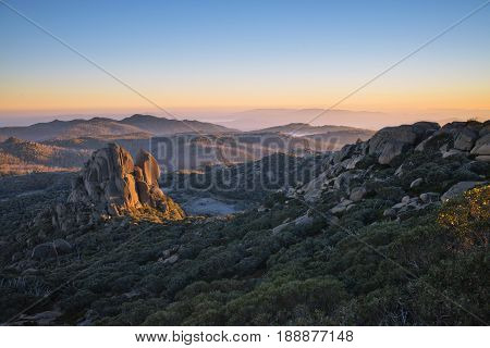 Sunrise as viewed atop a hiking trail known as 'The Hump' in Mt Buffalo National Park in the Victoria Australia alpine region. The rock formation is known as 'The Cathedral'