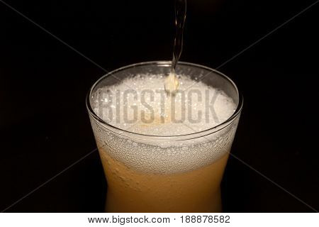 Beer in glass isolated on black background. Pour beer