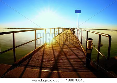 Morning In Harbor. Tourists Walk On Pier Above Sea. Clear Blue Sky, Smooth Water Level