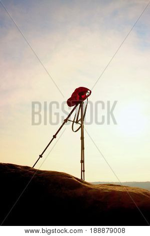 Tripod with red baseball cap on the peak ready for photography. Sharp autumn rocky peaks increased from gold fog. Vivid and strong vignetting effect.