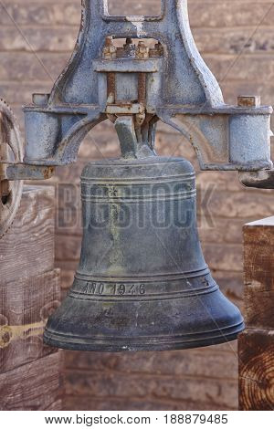 Antique bronze bell with mechanism on a bell tower. Vertical