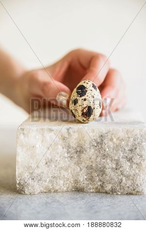 Close up woman's hand touching single quail egg on white piece of stone
