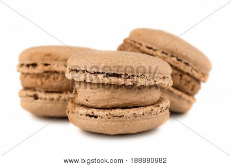 Three brown french macaroon cookies on white background