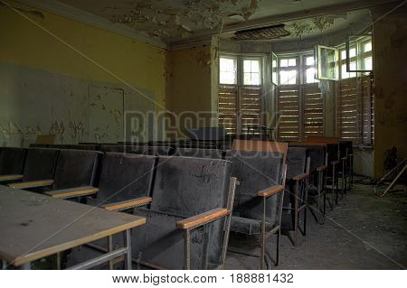 Empty chairs of old forgotten audience in ruined house.