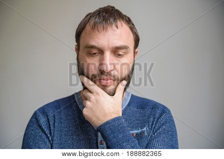 Thoughtful man in blue sweater touches his beard