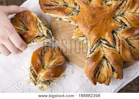 Poppy seed bread in the shape of a flower. Girls hand pick up a piece of bread from the table. Top view.