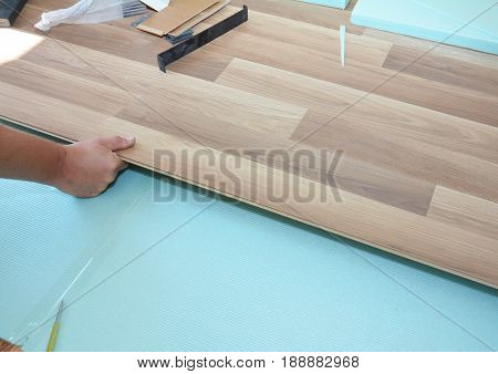 Contractor installing wooden laminate flooring with insulation and soundproofing sheets. Man laying laminate flooring. Man laying laminate flooring.